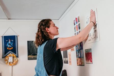 Student hangs art print on wall.