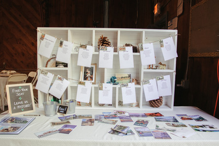 Wide angle shot of a campy wedding decorations: table settings hanging near postcards, stuffed animals, and camping photos.