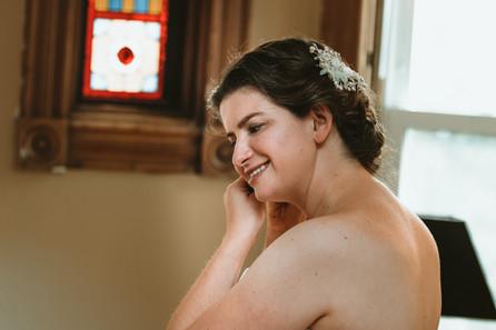 Bride puts in earing.