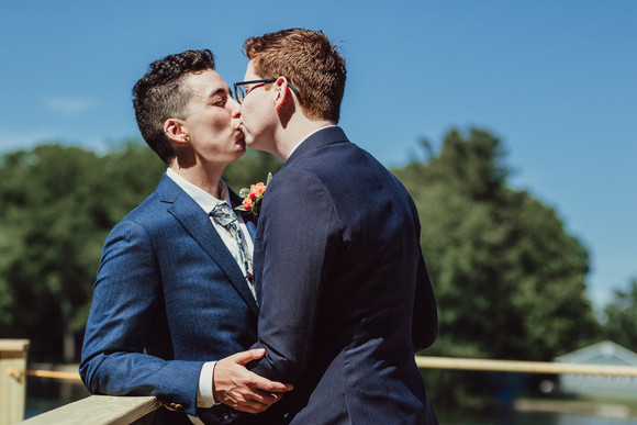 LGBTQIA couple kisses on a dock.
