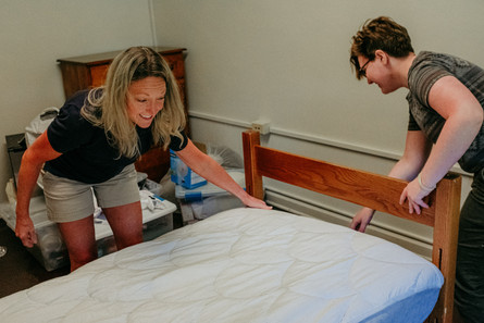 Parent and child place padding on their dorm room bed as they unpack.