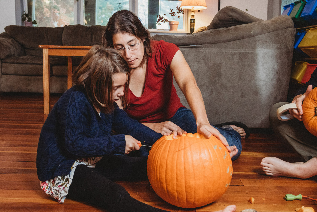 Mother and daughter carve a pumpkin