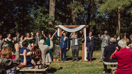 Wedding party holds hands and raises them up together in celebration.
