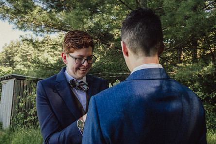 Queer couple in navy blue suits pin each others floral boutonnieres on each others lapels.