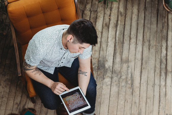 Graphic designer, Taylor Smaldone. Portrait taken from above looking down, showing him working on a project on his tablet.