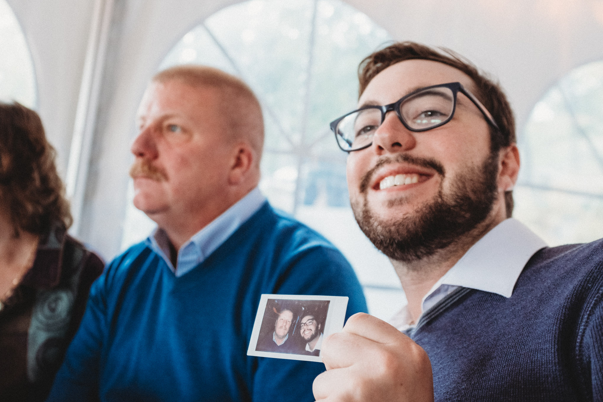 My younger brother Austin holds up a polariod of him and his dad, who sits behind him, unamused.
