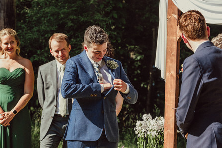 Afab queer person removes vows from suit jacket.