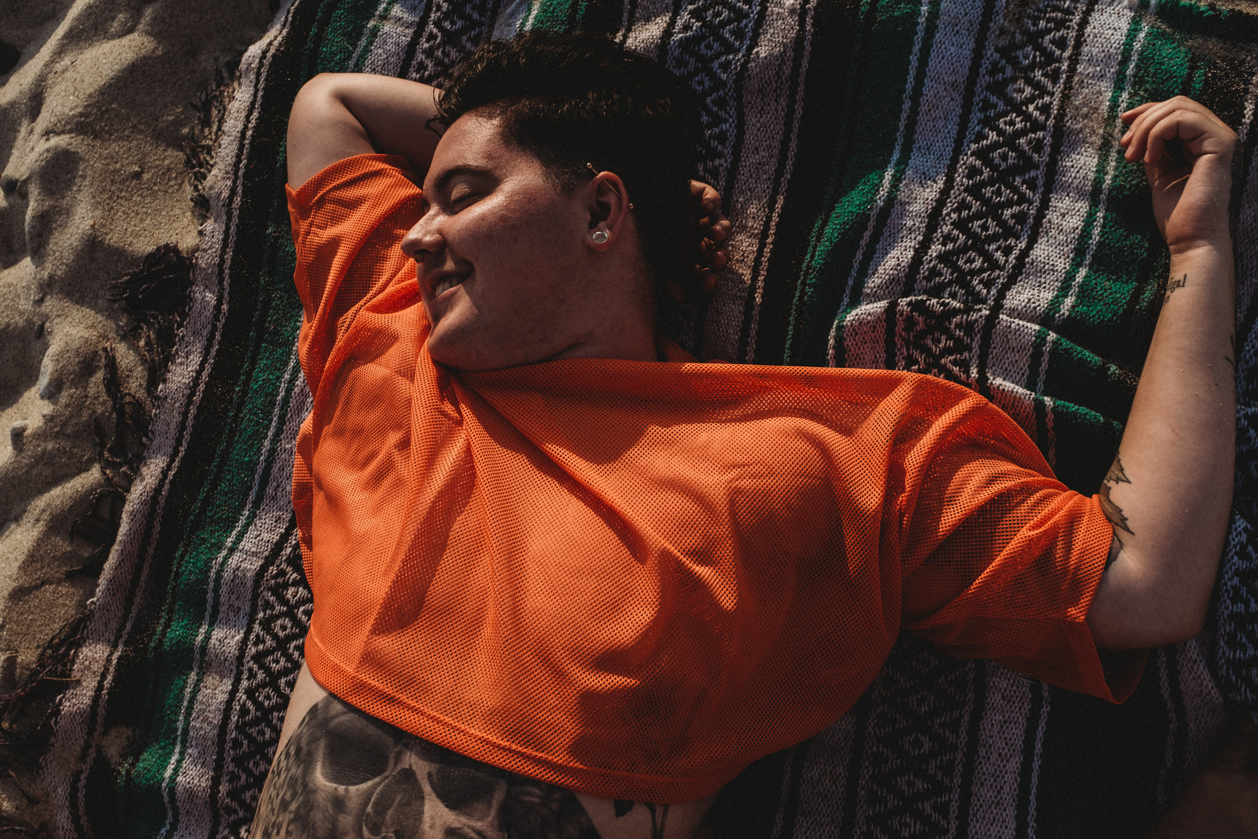 Sage laying down on the beach in a neon orange mesh crop top