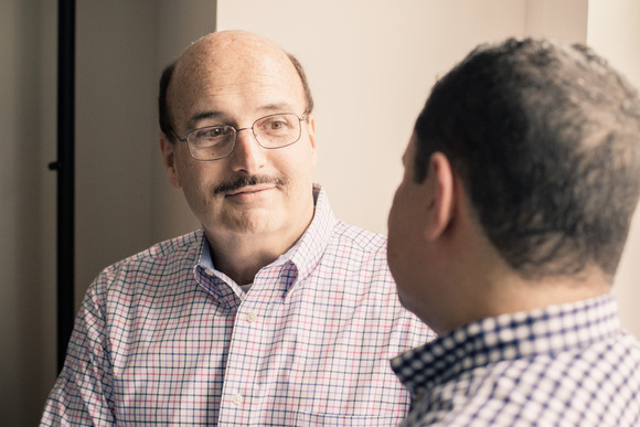 Bald gay man with a mustache smilling at his partner.