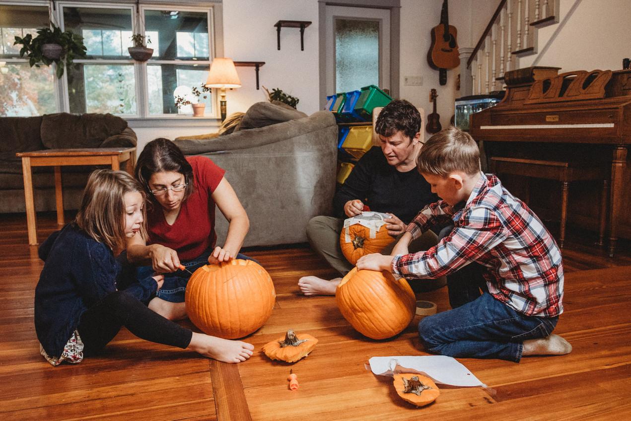 Family carves pumpkin together