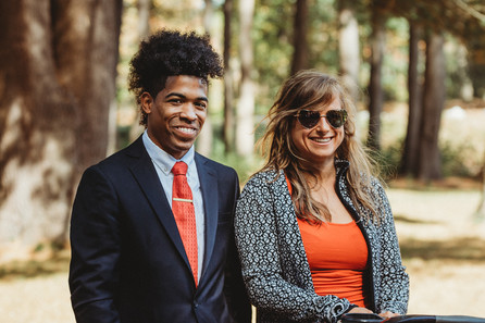 Sharply dressed interracial couple smiles. They both match with orange in their outfit.