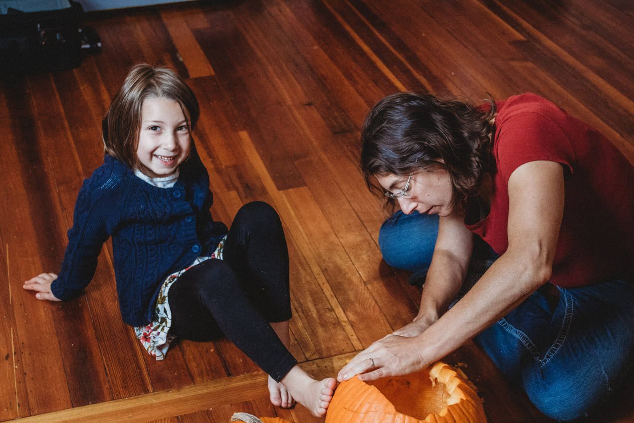 Daughter sits on floor and smiles