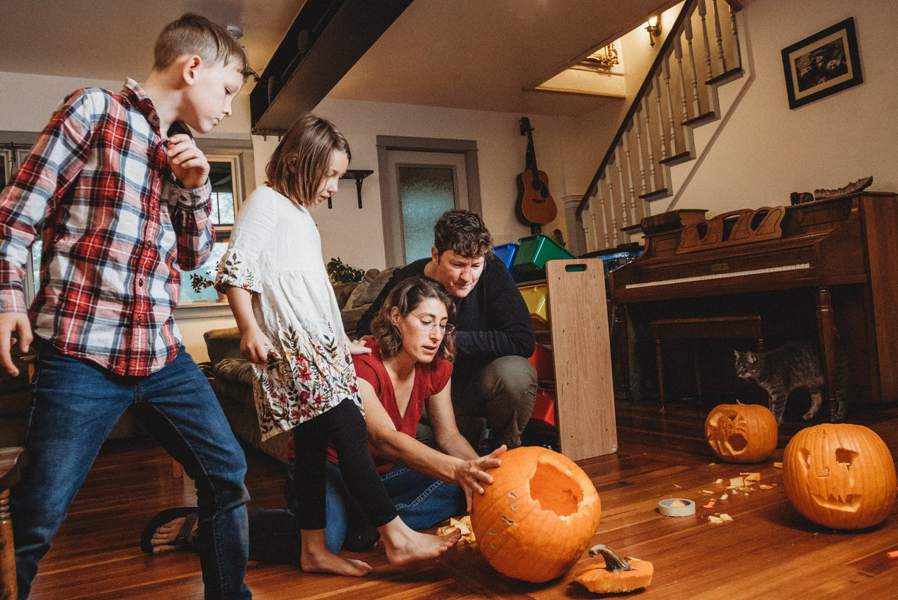 Photo journalistic queer family portrait as children look to see the pumpkin that their mothers carved