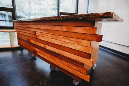 The desk that the students and staff collaborated on. The front is covered in reclaimed flooring materials,  each engraved with the name of the students who worked on the desk.