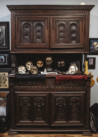 Ornate cabinet filled with human skulls.
