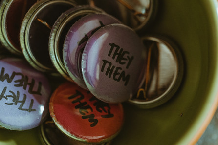 Pronoun pins where the party favors. Pictured: a bowl with they / them pronouns in purple or pink.