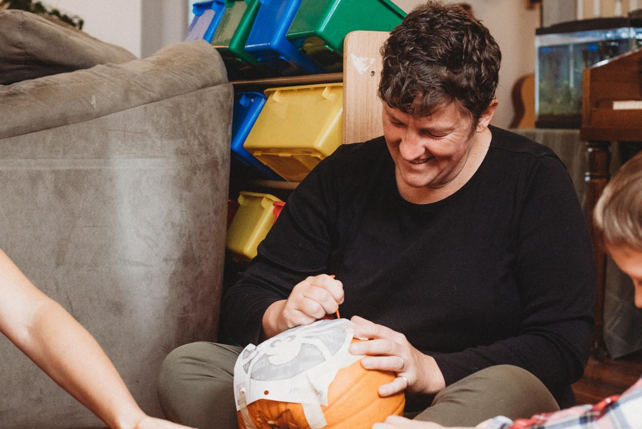 Denise smiles as she carves a pumpkin