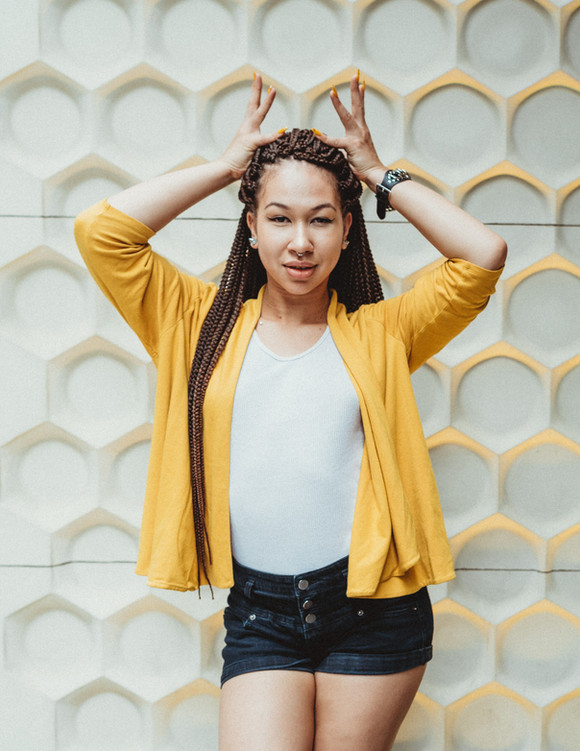 Dancer Jazzmine Divvine wearing a yellow and white outfit whith a honey comb wall behind her.