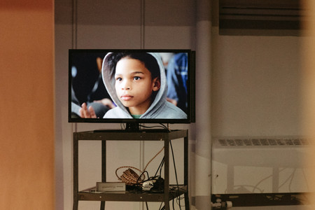 TV playing a video on the history of standardized testing. The screen shows the face of a young black boy