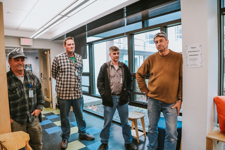 Four members from Mount Holyoke College's facilities department stands near by as they listen to the students discuss the collaborative process of building the desk.