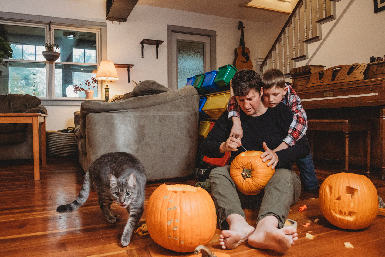 Son hugs his mother as she carves pumpkins. Cat walks by licking lips