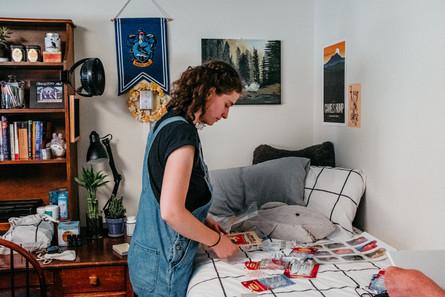 Student organizes prints before hanging them.
