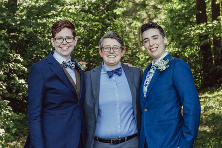 LGBT couple poses with their officiant.