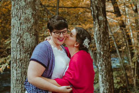 Lesbian couple snuggles in close and kiss.