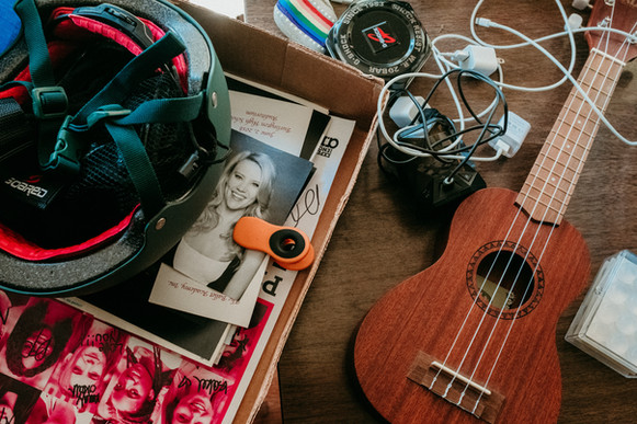 All the move in essentials: a ukulele, skateboard helmet, charging cables, and a picture of Kate McKinnon.