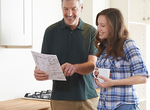 Woman With Carpenter Looking At Plans Fo