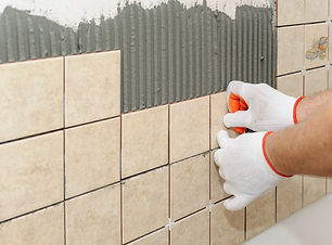 Worker putting  tiles on the wall in the