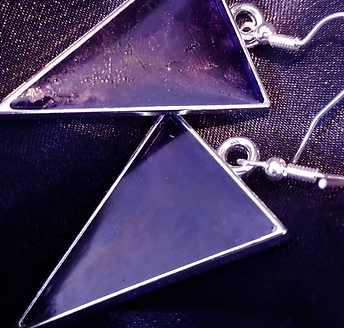 A pair of cone shapes earrings in purple on a black silk background.