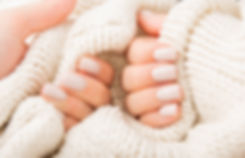 Stylish pastel beige Nails holding knitt