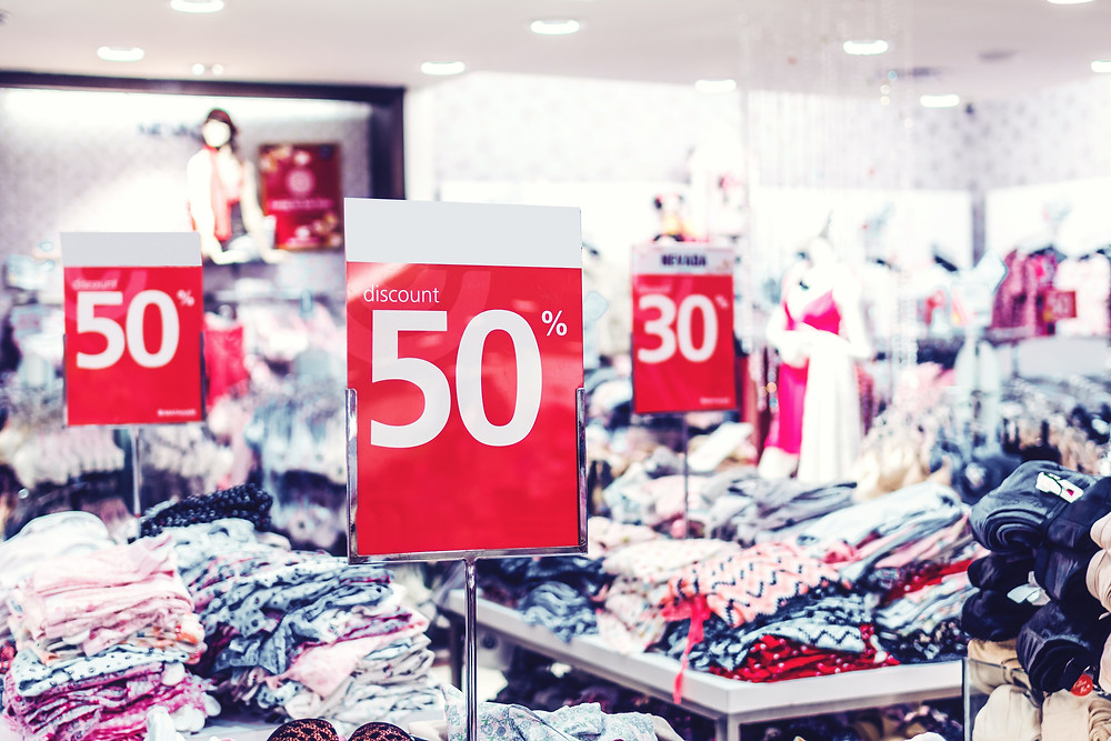 Image of clothing in piles on tables with 50% off signs.