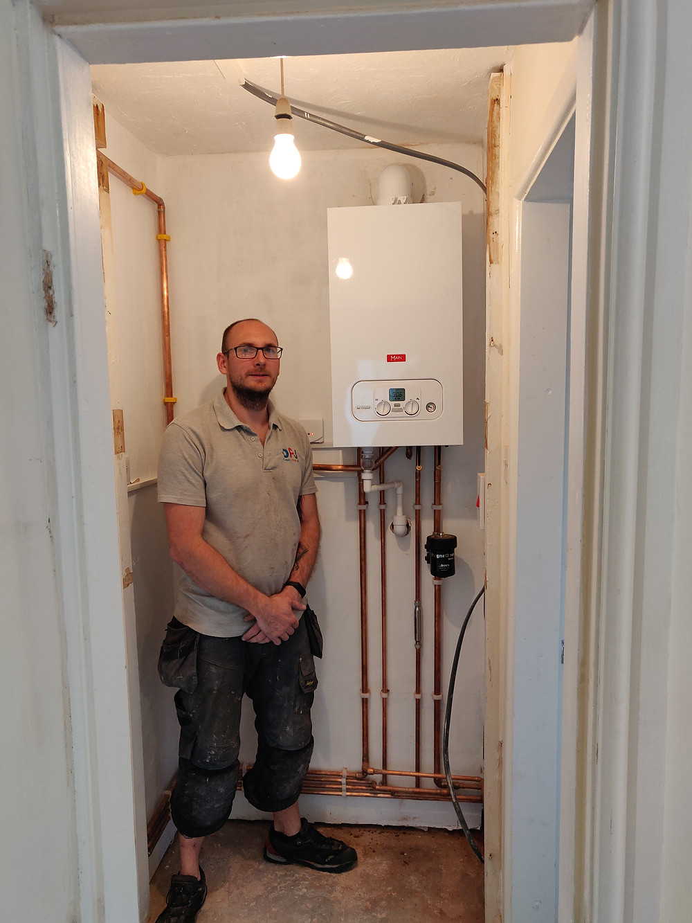 Dan Jackson next to the new Main Eco Compact Combi boiler installation for a landlord in Rugeley