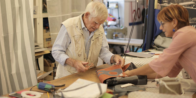 aged-craftsman-making-leather-bag-in-wor