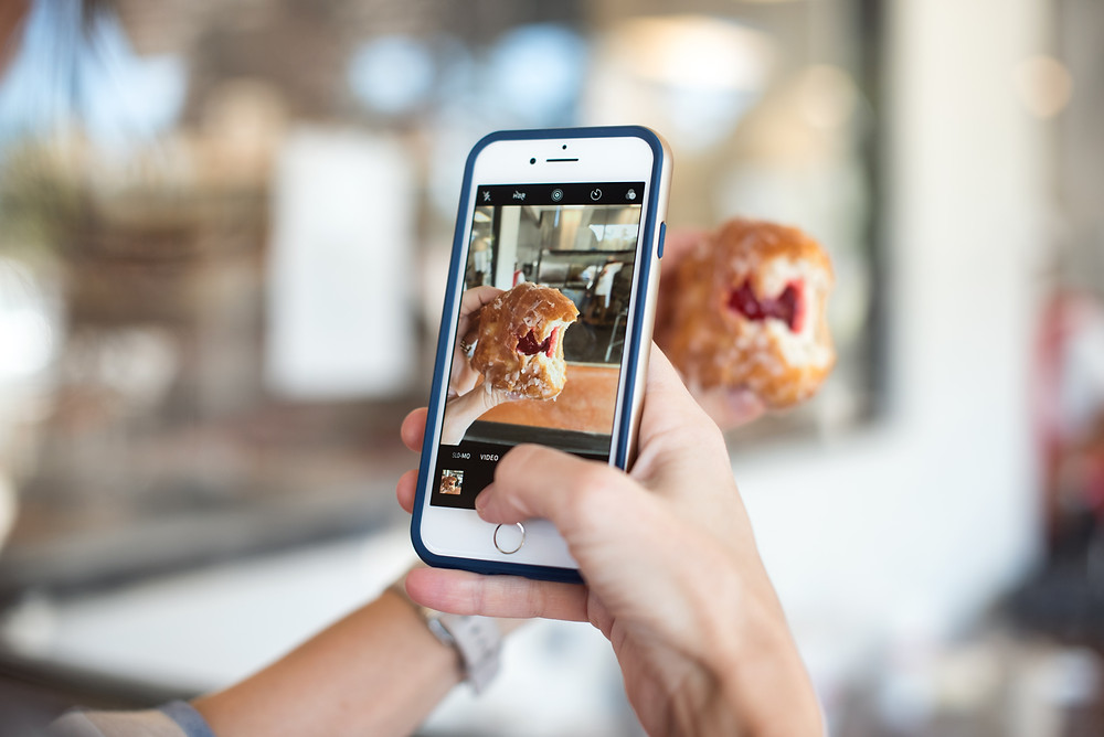 A person taking a photo of their pastry