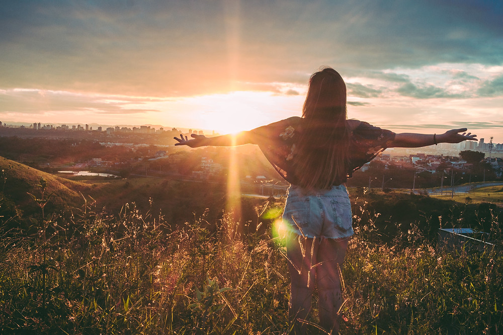 Woman stands with outstretched arms on mountain over field at sunrise