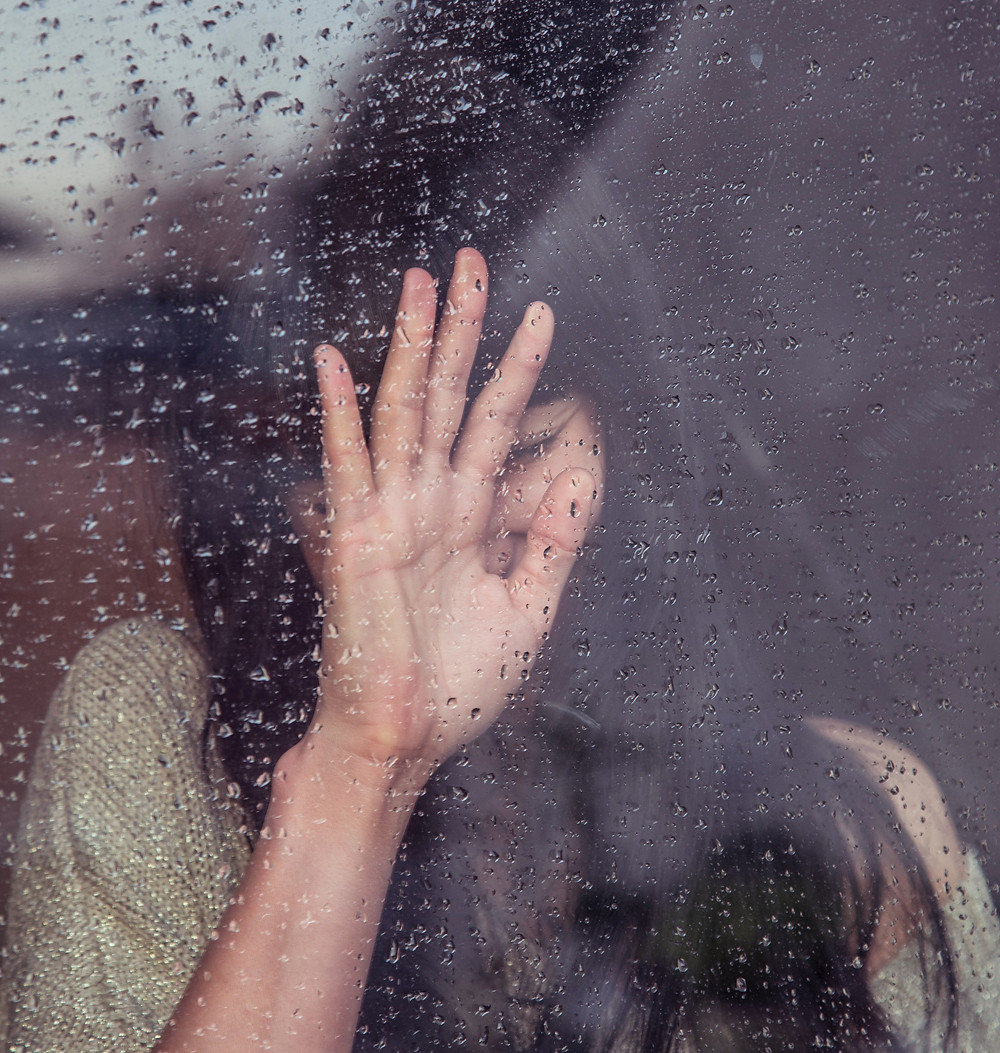 Woman with her eyes closed touches window with rain drops