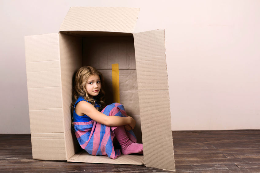Sad little girl sitting in a box