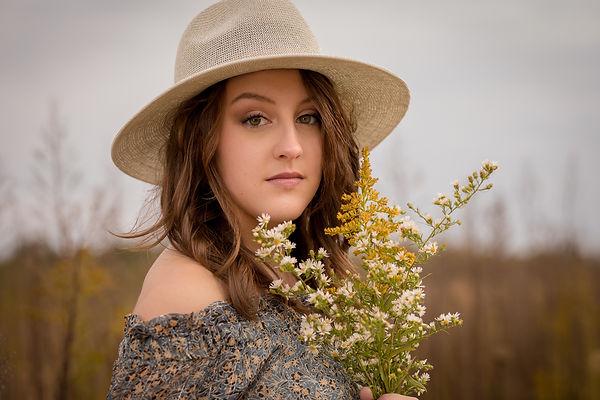 teen holding flowers in field.JPG