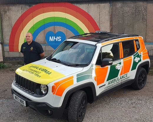 Ambulance in front of NHS rainbow