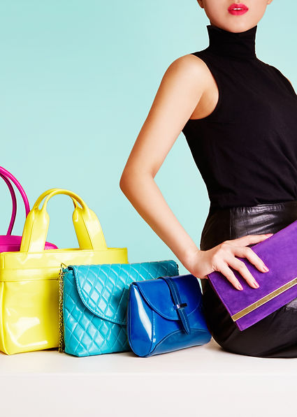 Woman sitting with colorful bags. leathe