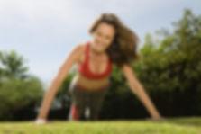 Femme vue de face, en tenue fitness, en position pompes