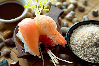 Image of salmon and shrimp sushi with rice over a natural material background.