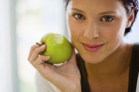 une femme qui tient une pomme verte