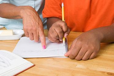 Una docente enseñándole a un niño a escribir