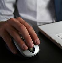 Primer plano de una mano sobre un mouse junto al ángulo de una notebook.