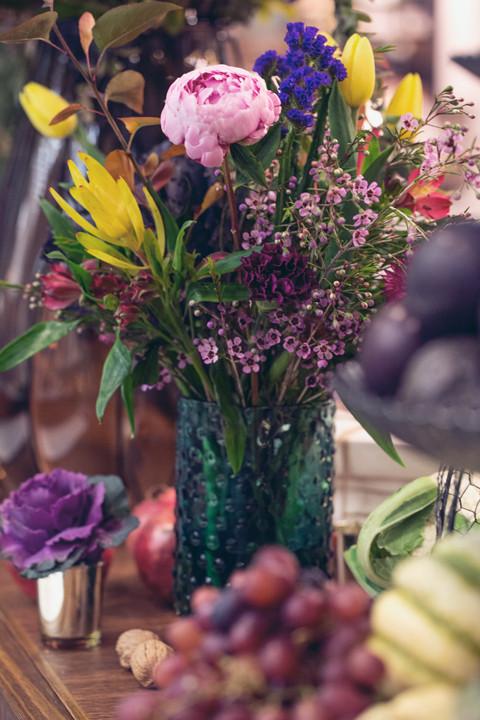 Stunning wildflower arrangement in teal glass vase