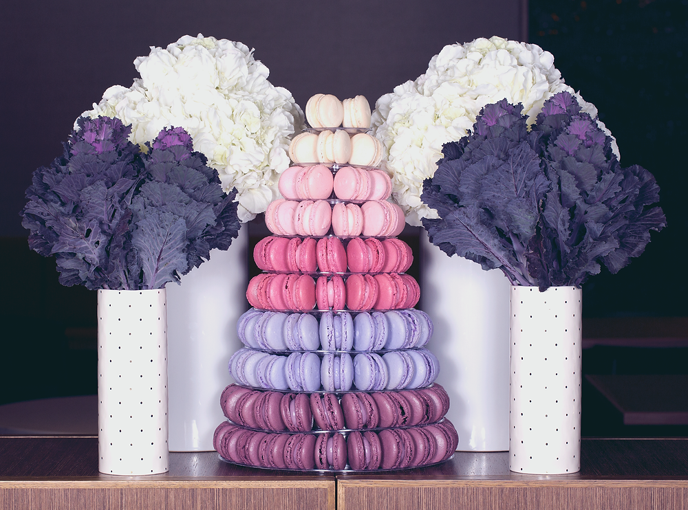Tower of macaroons framed by vases of purple and white blooms